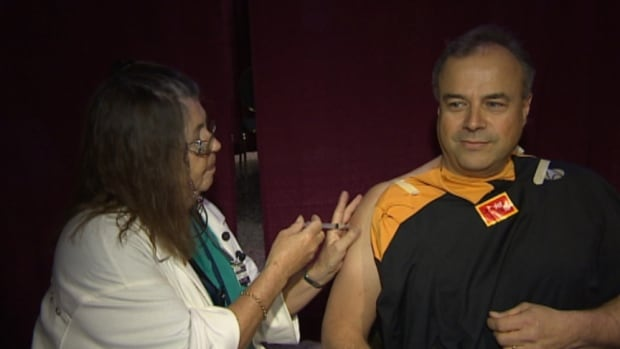 Real Cloutier, right, vice-president and chief operating officer of the Winnipeg Regional Health Authority, got his flu shot at the Central Canada Comic Con on Friday afternoon.