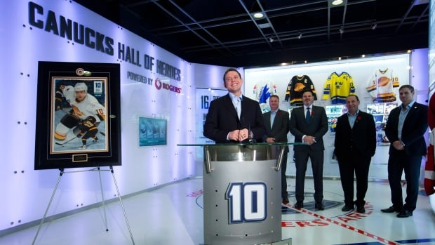 """Retired Vancouver Canucks' forward Pavel Bure, centre, smiles while speaking after the NHL hockey team inducted him into their """"Hall of Heroes"""" in Vancouver, on Friday. The Canucks will retire Bure's number 10 Saturday night before a game against the Toronto Maple Leafs on Hockey Night in Canada. Standing behind him are, from left to right, Canucks' president and general manager Mike Gillis, team co-owner Francesco Aquilini, director of player development Stan Smyl and former player Markus Naslund."""
