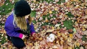 Girls playing in autumn leaves