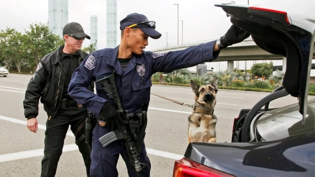Los Angeles Airport officer Daniel Keehne, left, and his dog Axa, and officer Fritz Corros inspect a car trunk at an access road checkpoint outside Los Angeles International Airport on Monday.