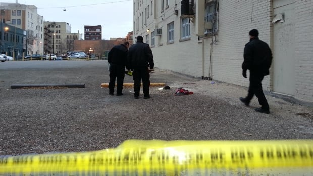 Police investigators examine the scene on Tuesday where a man was found injured beside the Royal Albert Hotel just before 12 a.m. He later died in hospital.