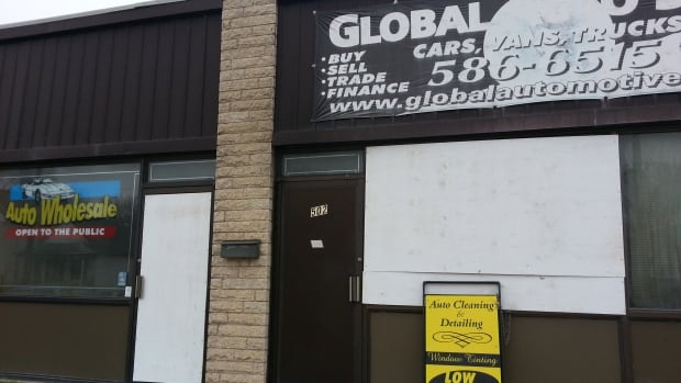 The windows are boarded up at Global Auto Sales on Tuesday, following a fire that caused $500,000 in damage.