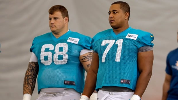 In this July 24, 2013 file photo, Miami Dolphins guard Richie Incognito (68) and tackle Jonathan Martin (71) take part in practice in Davie, Fla.
