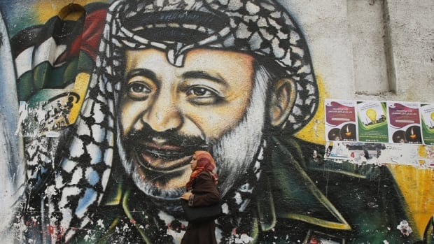 A Palestinian student walks past a mural depicting late Palestinian leader Yasser Arafat in Gaza City November 7, 2013. Swiss scientists who conducted tests on the remains of Palestinian leader Yasser Arafat, whose widow Suha says he was poisoned by radioactive polonium, has confirmed that his death was not accidental.