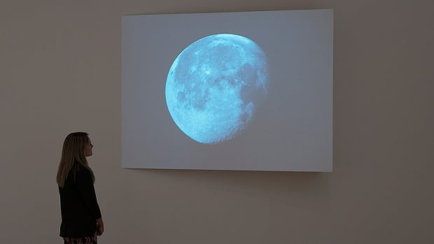 A woman examines Erin Shirreff's 2010 video artwork Moon. The Kelowna-born, New York-based artist is the 2013 winner of the Aimia | AGO Photography Prize.