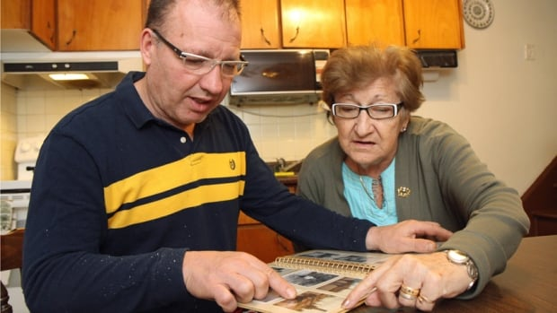 Walter Furlan and his mother Dirce pore over old family photos at her home in Hamilton's Parkdale neighbourhood on Thurs. Nov. 7.