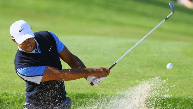 Tiger Woods plays a shot from a bunker near the 13th green during first-round play of the Turkish Open in Belek on Friday. Woods shot a nine-under 63 to trim a six-shot deficit to one.