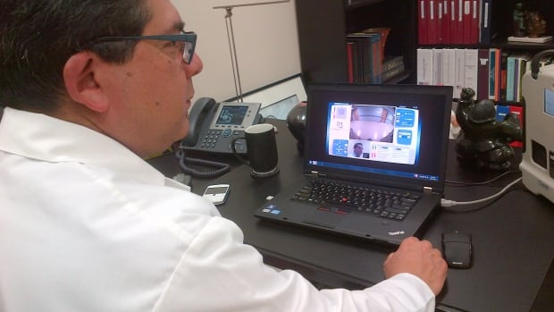 """Dr. Ivar Mendez links with his robotic """"doctor in a box"""" in the Ile-a-la-Crosse health centre through his laptop at the College of Medicine in Saskatoon."""