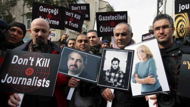 In this 2012, file photo,Turkish journalists holding photographs of their colleagues who lost their lives in Syria, from left, Anthony Shadid, Remi Ochlik and Marie Colvin, stage a protest outside the Syrian Embassy in Ankara.