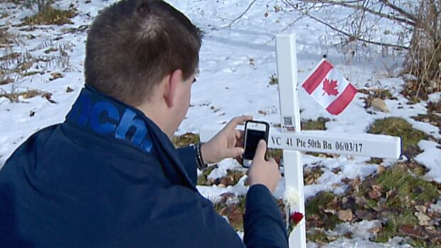 Brad Rains kneels before the cross containing the QR code for his great, great grandfather John George Pattison.