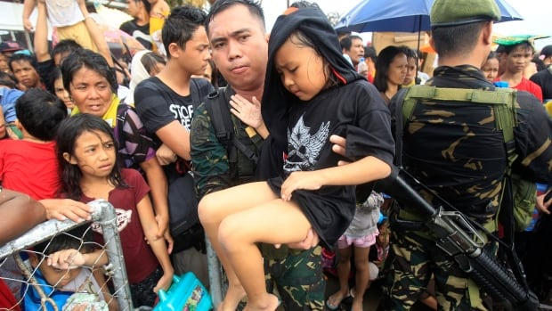 Philippine military personnel try to prioritize children and women first as they wait for evacuation flights in Tacloba in the central Philippines on Tuesday.