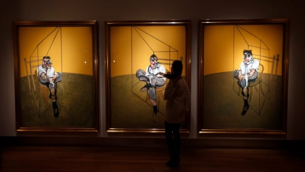 A Christie's staffer examines Francis Bacon's triptych Three Studies of Lucian Freud, which set a record for highest price paid for a painting at auction, going for $