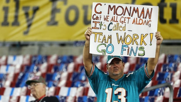 A Miami Dolphins fan holds up a sign prior to their game against the Tampa Bay Buccaneers at Raymond James Stadium on Monday.