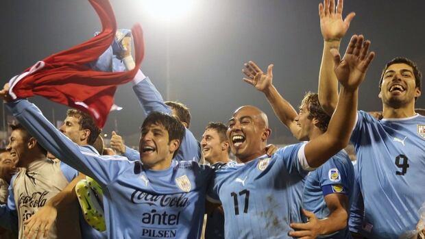 Uruguay players celebrate after winning their FIFA 2014 World Cup qualifier intercontinental playoff 1st leg match 5-0 over hometown Jordan on Wednesday in Amman.