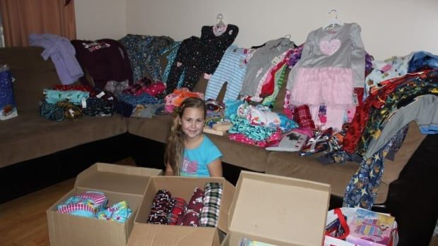 Eight-year-old Jorja Hinks is shown surrounded by donations of new pyjamas and books in her Goulds home.