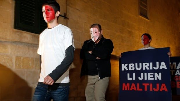 "Members of the Maltese opposition Nationalist Party's youth section protest Nov. 12 against a plan to allow the sale of citizenship to foreigners for 650,000 euros. The poster reads ""I am proud to be Maltese""."