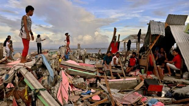 Residents gather amid the devastation in Tacloban, Leyte, Philippines as the country struggles to rescue survivors and get medical care and food to people affected by the typhoon.