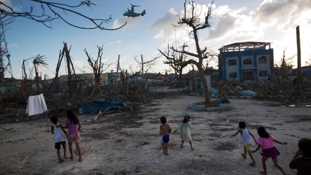 A U.S. military aircraft flies above the destroyed town of Guiuan on Thursday. Aid is still needed on many of the islands.