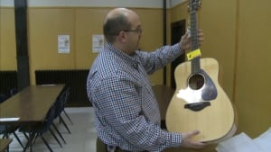 Dean Peckford holding a guitar, one of the silent auction items