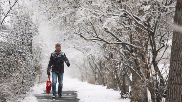 Kolja Vainstein walks along a snowy street in Calgary on Nov. 2. Parts of southern Alberta are under a snowfall warning for the third weekend in a row.
