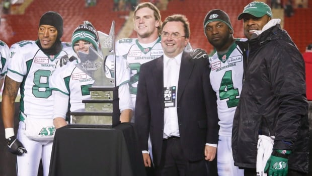 Saskatchewan Roughriders' players and staff, left to right, Geroy Simon, Weston Dressler, Craig Butler, general manager Brendan Taman, quarterback Darian Durant, and head coach Corey Chamblin pose with the West Final trophy after their victory in Calgary on Sunday.