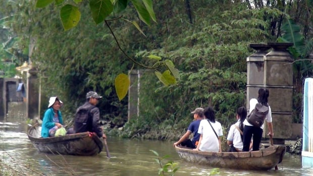 Small boats are used to ferry people through floodwaters in central Vietnam on Monday.  Several dozen people have died from flooding caused by heavy rains in central Vietnam, with about 80,000 people forced from their homes, disaster officials said Tuesday.