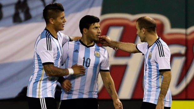 Argentina's Sergio Aguero, centre, is congratulated by teammates Marcos Rojo, left, and Rodrigo Palacio after scoring during the second half of an international friendly soccer match against Bosnia Monday in St. Louis.