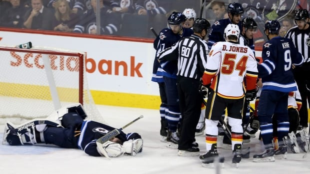 Winnipeg Jets' goaltender Al Montoya lays on the ice after being crushed by Calgary Flames' Lee Stempniak during the third period of their game in Winnipeg on Monday.
