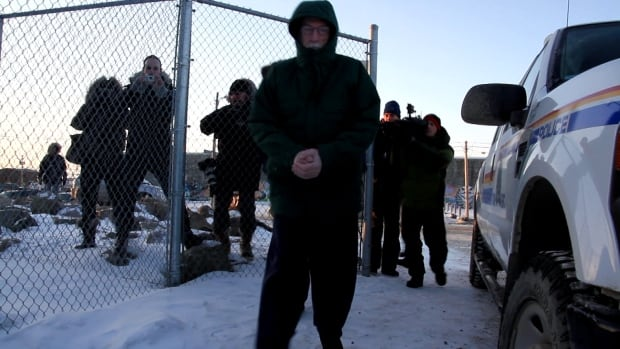 Eric Dejaeger is escorted outside the Nunavut Court of Justice in Iqaluit in November 2013.