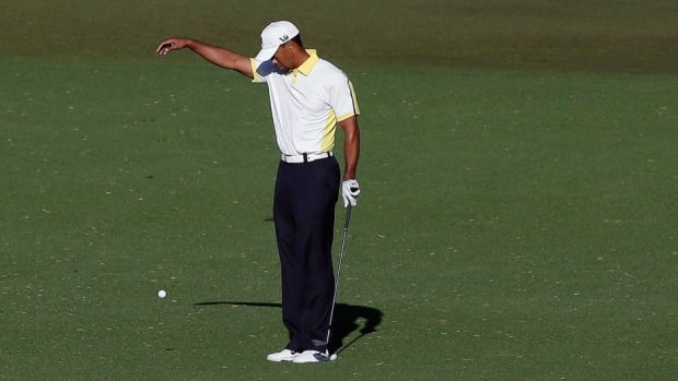 Tiger Woods takes a drop on the 15th hole after his ball went into the water during the second round of the Masters in Augusta, Ga., in April.