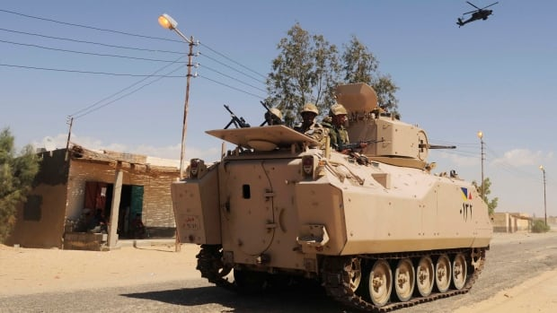Egyptian soldiers patrol in an armoured vehicle backed by a helicopter gunship during a sweep through villages in northern Sinai earlier this year. A suicide bomber killed soldiers in the area on Tuesday.