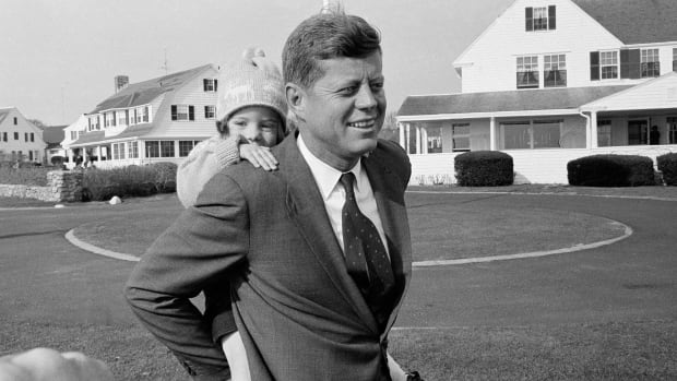 In this Nov. 9, 1960 photo, Caroline Kennedy gets a piggy-back ride from her father, Sen. John F. Kennedy, in Hyannis Port, Mass.