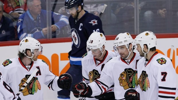 Chicago Blackhawks' Duncan Keith (2), Jonathan Toews (19), Patrick Sharp (10) and Brent Seabrook (7) celebrate Sharp's empty net goal against the Winnipeg Jets during third period NHL action in Winnipeg on Thursday, November 21, 2013. THE CANADIAN PRESS/John Woods