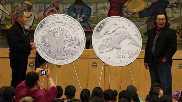 Royal Canadian Mint Board of Directors member Claude Bennett and Cape Dorset  artist Tim Pitsiulak unveil new 25-cent coins celebrating the 100th anniversary of the Canadian Arctic Expedition and Life in the North at Kullik Illihakvik Elementary school in Cambridge Bay.