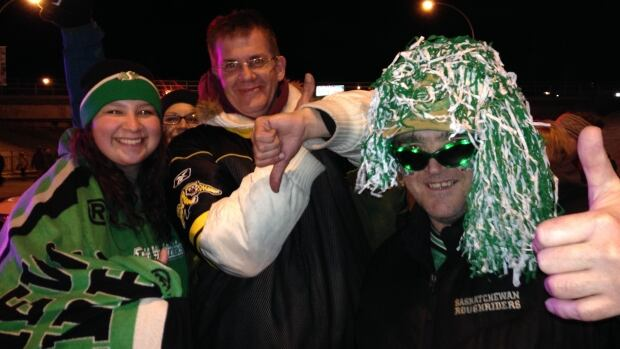"Hamilton Tiger-Cats fan Jeff May, centre, jokes around with Saskatchewan Roughriders fans in Regina after the Grey Cup on Sunday night. Though his team didn't win, May said the weekend has been ""such an experience."""
