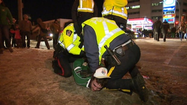 "Police restrained a man yelling ""Go Riders!"" on Sunday night. It wasn't immediately clear why he was being held."