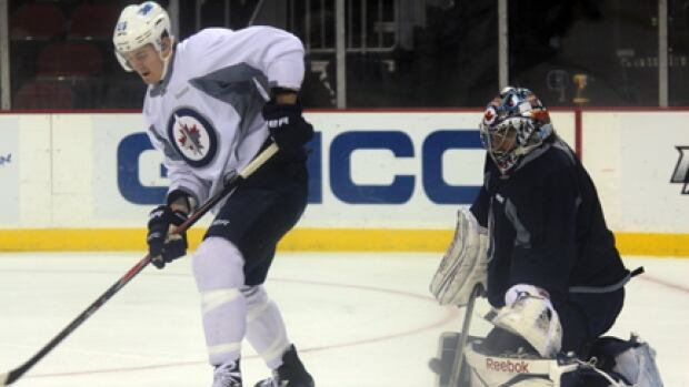 Forward Mark Scheifele gets in front of goaltender Al Montoya at during practice this morning in New Jersey.