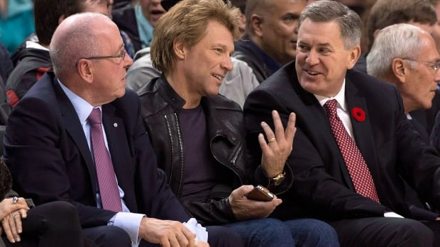 Maple Leaf Sports and Entertainment CEO Tim Leiweke (right) chats with Jon Bon Jovi as MLSE Chairman Larry Tanenbaum (left) looks on during first half NBA action between the Toronto Raptors and the Boston Celtics in Toronto on Wednesday October 30, 2013.