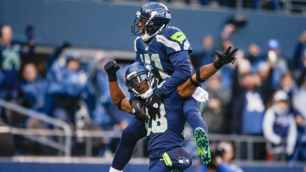Cornerback Walter Thurmond of the Seattle Seahawks, bottom, is congratulated by defensive back Byron Maxwell after returning an interception for a touchdown against the Minnesota Vikings at CenturyLink Field on November 17, 2013 in Seattle, Washington. Thurmond was suspended by the league on Tuesday for violating the NFL substance abuse policy.
