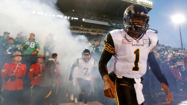 Hamilton Tiger-Cats quarteback Henry Burris, right, takes the field to meet the Saskatchewan Roughriders in the CFL's 101st Grey Cup championship football game in Regina on November 24, 2013. Burris, who becomes a free agent, says he wants to return to the Ticats next season.