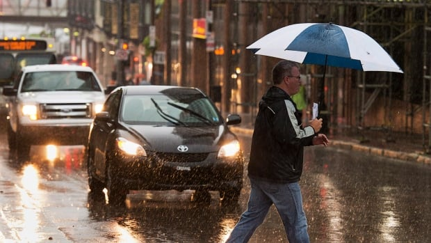 A pedestrian braves heavy rain in Halifax. Forecasters say the strongest winds, with gusts up to 100 kilometres an hour, are expected in western Nova Scotia and the Cape Breton Highlands.