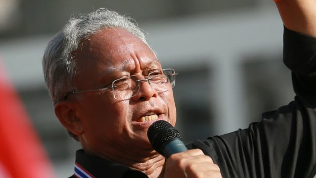 """Suthep Thaugsuban, a former deputy premier leading the protest movement, talks to anti-government protesters outside the Government complex in Bangkok, Thailand, Wednesday, Nov. 27, 2013. Flag-waving protesters vowing to topple the Thai prime minister took to the streets of Bangkok for a fourth day Wednesday, declaring they would take over """"every ministry"""" of the government. The brash threat is the boldest challenge yet to Yingluck Shinawatra's embattled administration, and it has raised fears of fresh political violence in the divided Southeast Asian nation. Late Tuesday, police issued an arrest warrant for Suthep. (AP Photo/Wason Wanichakorn)"""