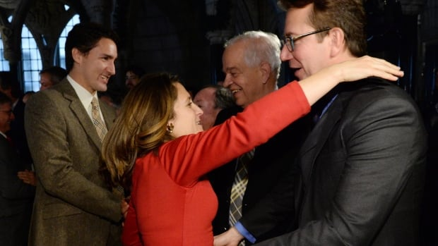 Liberal Leader Justin Trudeau, left, and newly-elected MP Chrystia Freeland are welcomed by the Liberal caucus on Parliament Hill in Ottawa on Wednesday, November 27, 2013. Freeland and Liberal MP Scott Brison, right, have been advising Trudeau on economic policy since he appointed them to an economic consultative committee in September.