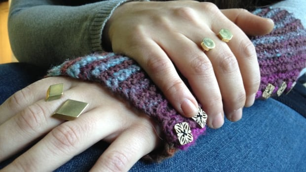 Winnipeg metalsmith Kat Pappas models two rings she handcrafted. Pappas is one of rotating roster of 100 artists and artisans who sell their wares at the Winnipeg Makers and Market. Pappas also wears one of a pair of hand knit arm warmers by Winnipeg's Nojo Knitting.