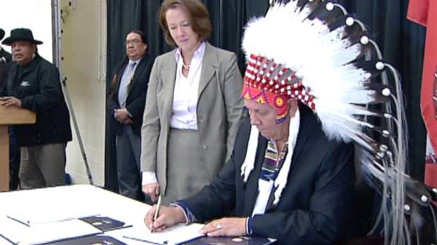 Chief Roy Whitney signs the 'historic' ring road agreement today as Alberta Premier Alison Redford stands behind.