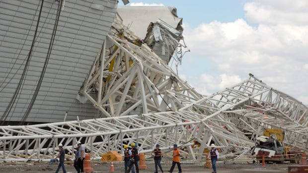 Civil defence and policemen inspect the damage of an accident at the Arena Corinthians, known locally as the Itaquerao, that will host the 2014 World Cup in Sao Paulo, Brazil, on Nov. 28, 2013.