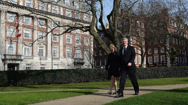 Prime Minister Stephen Harper walks through Grosvenor Square Garden with wife Laureen after attending Margaret Thatcher's funeral in London in April. The John A. Macdonald building, which was recently sold, can be seen at left.