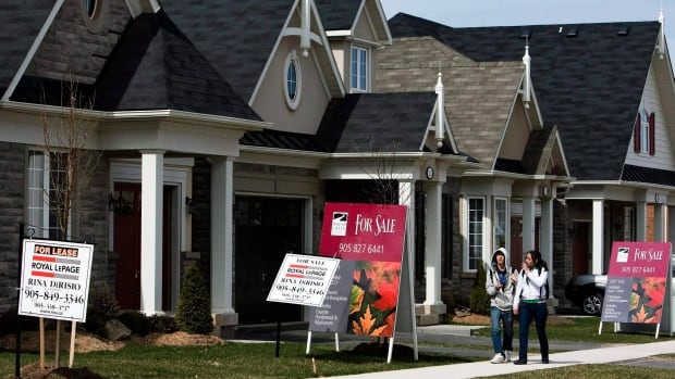 People walk past new homes that are for sale in Oakville, Ont. As home prices continue to rise across Canada, housing remains affordable in Sudbury, according to an analyst at the Canadian Mortgage and Housing Corporation. T