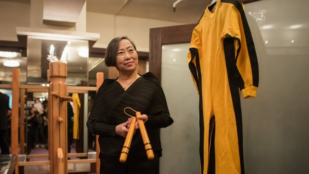Spink auction house vice chair Anna Lee poses with a jumpsuit worn by Bruce Lee and the nunchaku he used during the filming of 1972's Game of Death on Monday. A collection of personal articles from the life and career of Lee goes on sale Thursday, the 40th anniversary of his death.