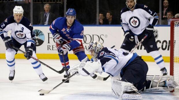Winnipeg Jets goalie Ondrej Pavelec makes a save as centre Olli Jokinen defends and New York Rangers left wing Chris Kreider skates toward the goal during the second period Dec. 2 in New York.